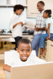 Son using laptop in the kitchen. Son using laptop against parents in the kitchen royalty free stock photo