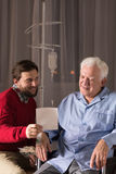 Son visiting disabled father. In nursing home royalty free stock image