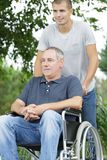 Son walking with disabled father in wheelchair at park. Man royalty free stock photos