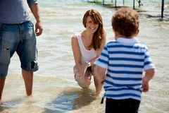 Son Walks Towards Mom in the Water. Mom smiling as her son walks towards her to dip in the water royalty free stock photo