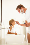 Son Watching Father Shaving In Bathroom Mirror. Smiling Royalty Free Stock Photos