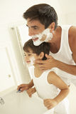 Son Watching Father Wet Shaving With Razor Royalty Free Stock Image