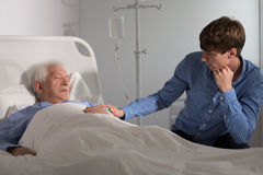 Son watching over his father. Elder ill men sleeping and a relative holding his hand Stock Photos