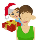 Son wearing santa hat giving to mother christmas gift covering her eyes with his hand Royalty Free Stock Images