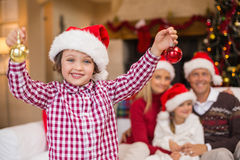 Son wearing santa hat holding baubles in front of his family. At home in the living room Royalty Free Stock Images