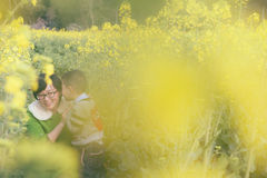 Son whisper with mother. Chinese boy whisper with mother by rape flower Royalty Free Stock Photography