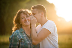 Son whispering a secret into mother`s ear. Adult boy sharing his secret with mother Royalty Free Stock Image