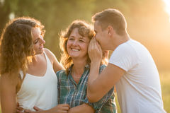 Son whispering sister`s secret into mother`s ear Stock Images