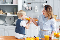 Son and young mother in the kitchen eating Breakfast. Boy drinking orange juice. Healthy food concept.  stock image