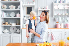 The kid closes his eyes orange. Fooling around. son and young mother in the kitchen eating Breakfast. Son and young mother in the kitchen eating Breakfast. Mom Stock Image