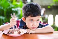 Sondage asiatique de petit garçon mangeant avec la nourriture de riz Image stock