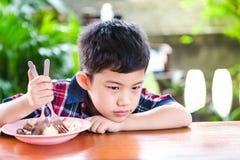 Sondage asiatique de petit garçon mangeant avec la nourriture de riz Photos stock