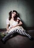 Sonderbares trauriges junges Mädchen mit den Puppen, die im schmutzigen Raum sitzen stockfotografie