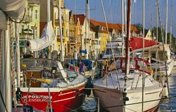 Sonderborg, Denmark - July 5th, 2012 - Sailing yachts at their moorings in the Sonderborg city harbor with colorful waterfront fac. Ades lit by the evening sun Stock Images