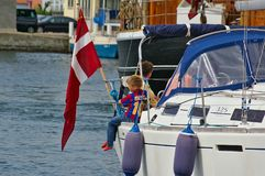 Sonderborg, Denmark - July 5th, 2012 - Young boy with soccer shirt sitting on the gunwale of a white sailing yacht with the Danish. Sonderborg, Denmark - July Stock Photo