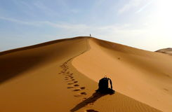 Sonderkommando der Rückseite und des Wanderers, die zur Spitze der großen Sanddüne im roten Dünenmeer des Ergs Chebbi, Marokko kl Stockbild