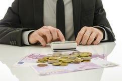 Vorderansicht des Geschäftsmannes arbeitend im Taschenrechner Stockbild