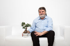 Sondern Sie alte Männer auf weißer Couch mit einem Bonsai aus Lizenzfreies Stockfoto