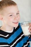 Sondern Sie blonden Jungen mit Glas Milch nahe Mund aus Lizenzfreies Stockfoto