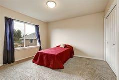 Sondern Sie rotes Bett im leeren Schlafzimmer im zweiten Stock aus Stockfotos