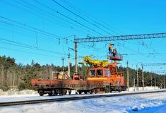 Sonderzug mit einem Landungskran für Service und Reparatur von elektrischen Netzen auf der Eisenbahn stockfotos
