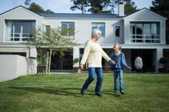 Sondotter och farmor som tillsammans dansar i trädgård Arkivbild