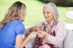 Sondotter som ger mediciner till lyckligt royaltyfri bild
