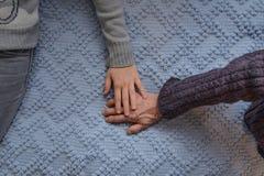 Sondotter som rymmer försiktigt hennes hand över hennes grandmother'shand Royaltyfri Foto