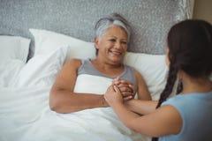 Sondotter som tröstar den sjuka farmodern i sängrum arkivfoton