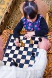 Sondottern spelar schack med hans farfar farfadern undervisar för att spela royaltyfri foto