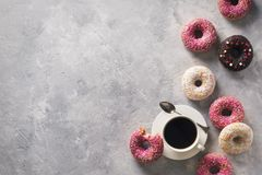 Sone pink and white donuts with cup of coffee over grey stone te royalty free stock image