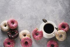 Sone pink and white donuts with cup of coffee over grey stone te royalty free stock photos