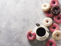Sone pink and white donuts with cup of coffee over grey stone te stock photos