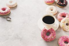 Sone pink and white donuts with cup of coffee over white stone t stock image