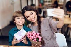 Sonen gratulerar hans moder på 8th mars Fotografering för Bildbyråer
