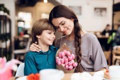 Sonen gratulerar hans moder på 8th mars Arkivbild