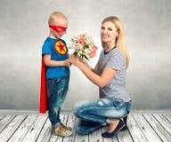 Sonen i dräkten av en superhero ger hans moder en bukett av blommor arkivfoto