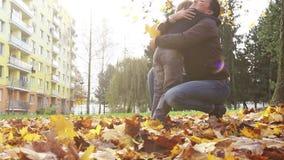 Sonen kommer till hans mum, kramar henne och ger henne en packe av gula höstsidor stock video