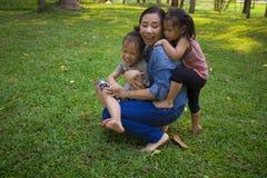 Sonen och dottern f?r livsstilst?endemamma i lycka p? yttersidan i ?ngen, den roliga asiatiska familjen i ett gr?nt parkerar fotografering för bildbyråer