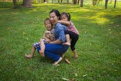 Sonen och dottern f?r livsstilst?endemamma i lycka p? yttersidan i ?ngen, den roliga asiatiska familjen i ett gr?nt parkerar arkivbild