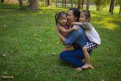 Sonen och dottern f?r livsstilst?endemamma i lycka p? yttersidan i ?ngen, den roliga asiatiska familjen i ett gr?nt parkerar arkivfoton