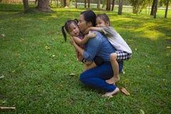Sonen och dottern f?r livsstilst?endemamma i lycka p? yttersidan i ?ngen, den roliga asiatiska familjen i ett gr?nt parkerar royaltyfria bilder
