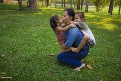 Sonen och dottern f?r livsstilst?endemamma i lycka p? yttersidan i ?ngen, den roliga asiatiska familjen i ett gr?nt parkerar royaltyfri foto