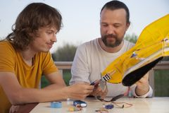 Sonen och fadern gjorde hemlagat radio-kontrollerat modellflygplan ai royaltyfri bild