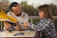 Sonen och fadern gjorde hemlagat radio-kontrollerat modellflygplan ai royaltyfria bilder