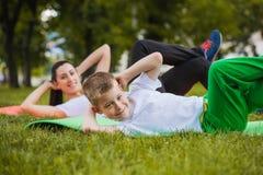 Sonen och modern gör övningar i parkera Royaltyfri Bild