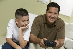 Sonfather Playing Video Game. Son with father Playing Video Game on sofa in living room royalty free stock photo
