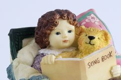 Song book. Ceramic doll with a bear reading a book Royalty Free Stock Photo