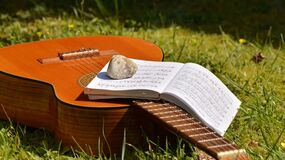 Song Book on Brown Classical Guitar on Green Grass during Daytime Royalty Free Stock Photos