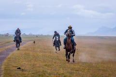 Riders galloping in rain, Kyrgyzstan Royalty Free Stock Photo